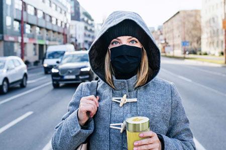Vrouw met mondmasker bamboe drinkbeker